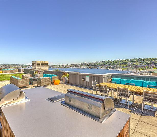 Downtown Seattle apartments - Neptune Rooftop lounge area with grills and views of Lake Union